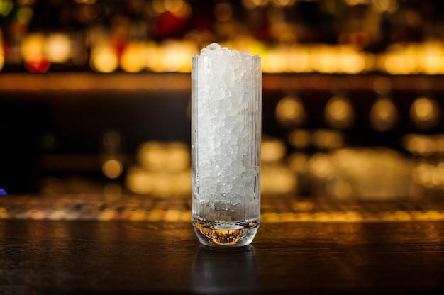 Grand verre à cocktail à paroi épaisse de glace pilée debout sur le support de bar en acier vide