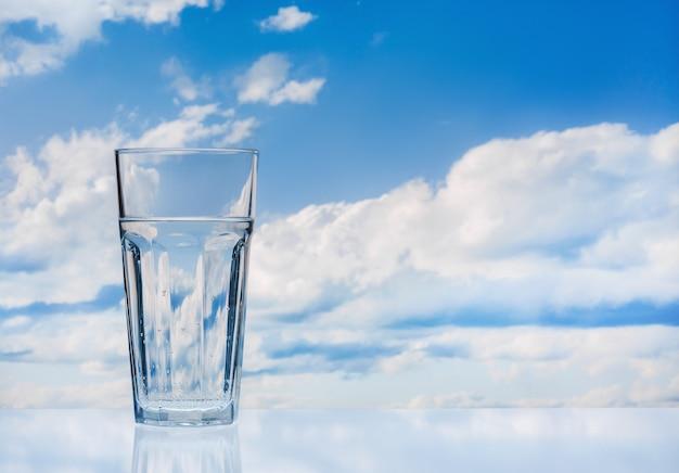 Grand verre d'eau douce contre le ciel bleu avec des nuages. surface réfléchissante. copiez l'espace.
