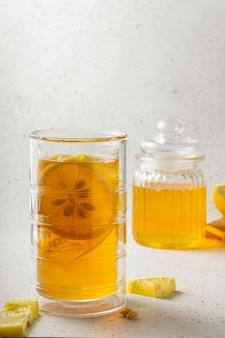 Grand verre de thé glacé au citron avec un pot de miel sur fond gris