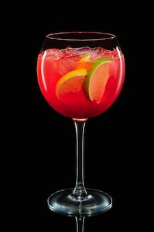 Grand verre à vin rond avec sangria aux agrumes sur fond noir