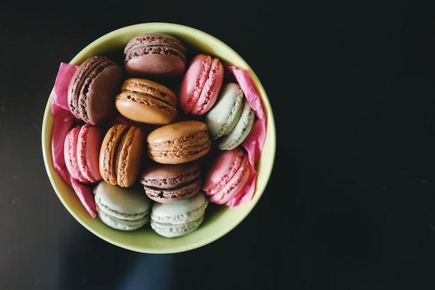 Grande assiette de macarons brillants et savoureux sur fond noir