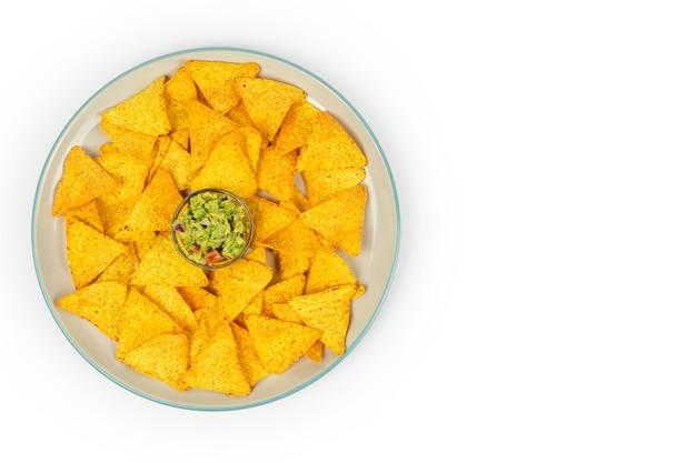 Une grande assiette avec des nachos croustillants et des chips de guacamole au centre du plat sur une assiette blanche