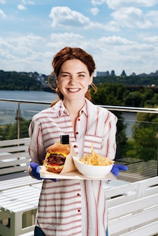 Grande assiette. rayonnant jeune femme portant des gants bleus tenant grande assiette avec double hamburger avec pommes de terre ami
