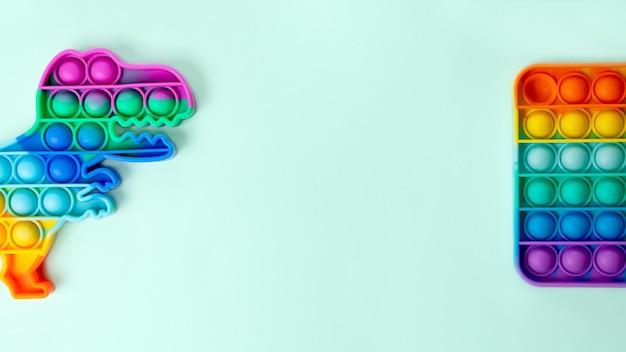 Grande bannière avec espace de copie avec deux jouets pop it dessusjouet en forme de dinosaure et rectangulaire
