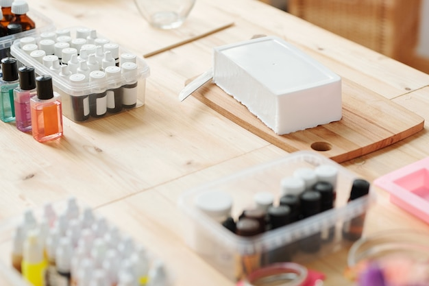 Grande barre de masse de savon dur blanc sur planche de bois entourée de bouteilles avec divers parfums et huiles essentielles