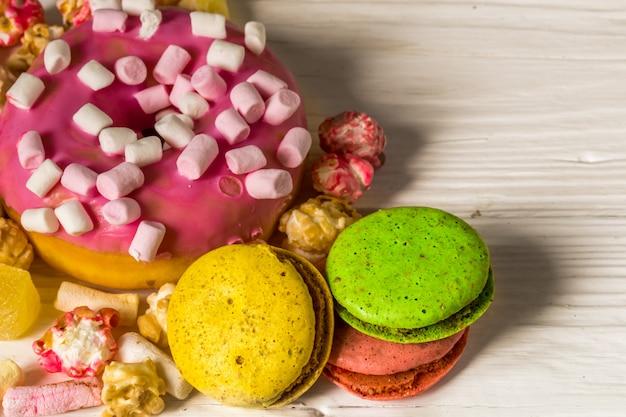 Grande belle boîte rose avec des bonbons sur table en bois