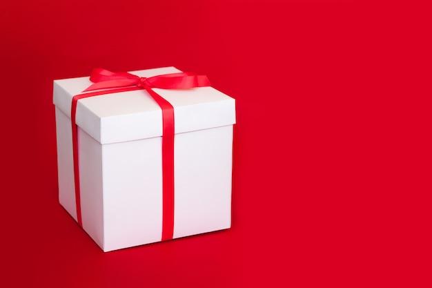 Grande boîte blanche avec un ruban rouge sur un rouge. concept de grande vente