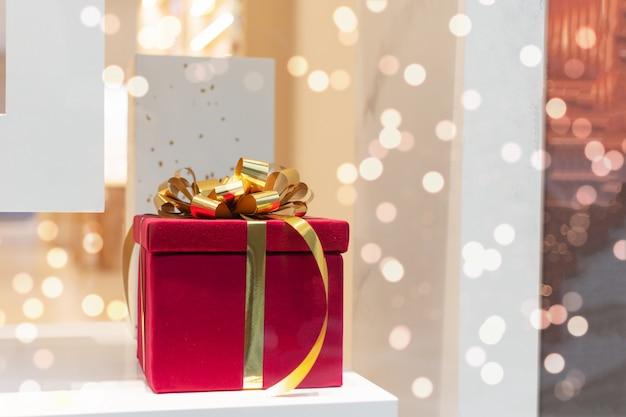 Grande boîte-cadeau décorée d'un noeud de ruban doré sur une table blanche sur des lumières bokeh lumineuses.