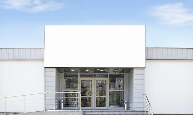 Grande boîte rectangulaire blanche vierge sur boutique, fond de ciel