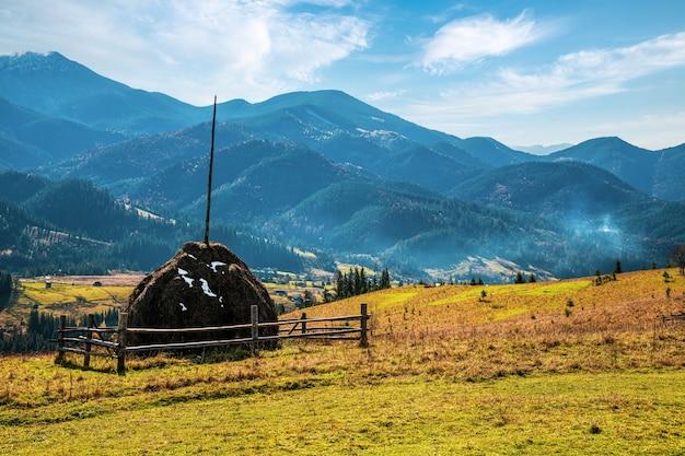 Une grande botte de foin dans le contexte de la nature merveilleuse des carpates et du ciel extraordinaire