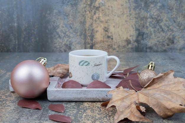 Grande boule de noël avec tasse de thé sur planche de bois.