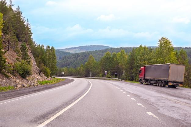 Une grande camionnette se dresse au bord de la route parmi les montagnes et les forêts