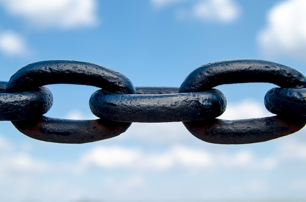 Grande chaîne noire sur ciel bleu, gros plan. chaîne en métal large faite de tore