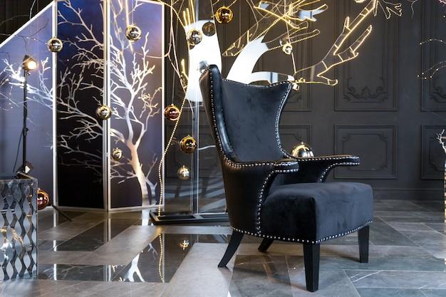 Grande chaise noire sur fond lumineux de guirlandes lumineuses. produits à thème de noël, salle du nouvel an avec