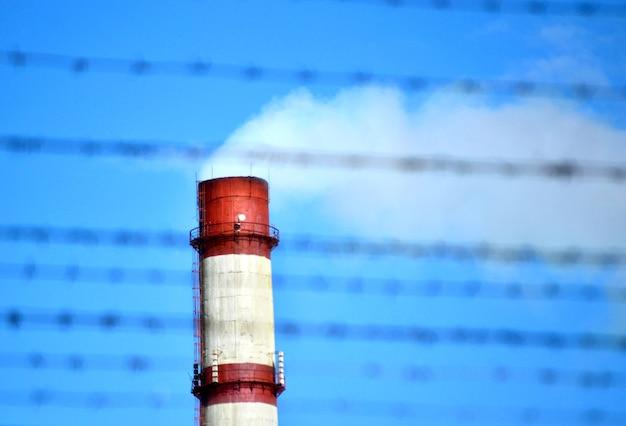 Grande cheminée avec de la fumée derrière les barbelés