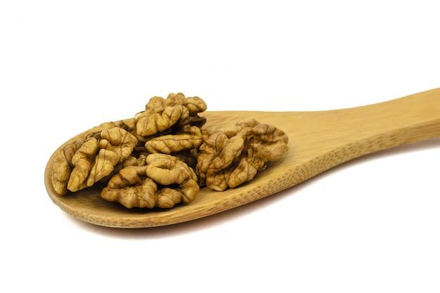 Grande cuillère en bois aux noix isolé sur fond blanc.