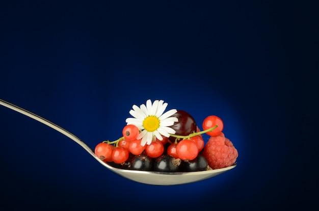 Une grande cuillère pleine de baies sauvages juteuses de groseille rouge, cerise, framboise, cassis et framboise, avec des feuilles vertes et une fleur de camomille sur un bleu. fraîcheur et été dans une cuillère.