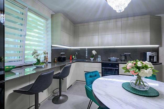 Grande cuisine moderne blanche et grise avec table à manger