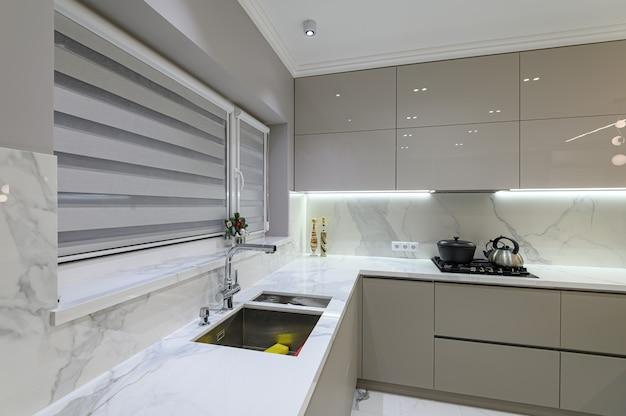 Grande cuisine moderne de luxe en marbre blanc unie avec salle à manger