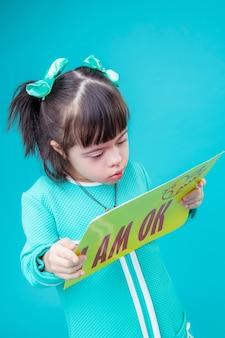 Grande curiosité. enfant curieux aux cheveux noirs souffrant de troubles mentaux portant une affiche avec une promesse importante