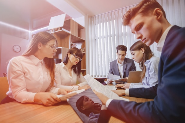 Une grande équipe de personnes travaille à une table pour les ordinateurs portables, les tablettes et les papiers, un grand téléviseur sur un mur en bois