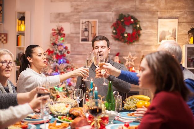Grande famille à la célébration du dîner de noël profitant du temps ensemble et trinquant un verre de vin.