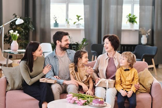 Grande famille de cinq personnes assises sur un canapé dans un environnement familial