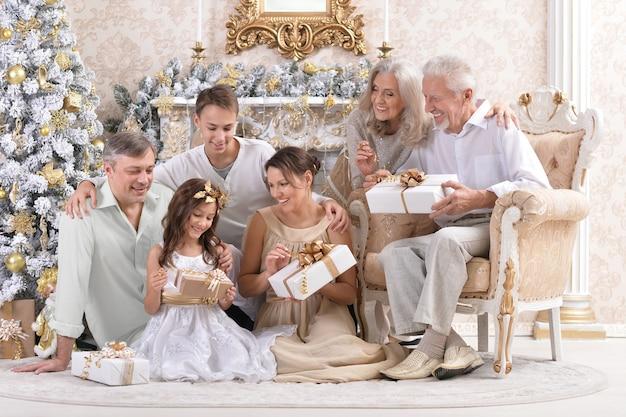 Grande famille heureuse célébrant le nouvel an à la maison assise sur un canapé avec des coffrets cadeaux