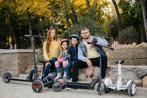 Une grande famille heureuse monte des segways et des scooters électriques dans le parc par une chaude journée d'automne au coucher du soleil. vacances en famille dans le parc.