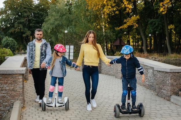 Une grande famille heureuse monte des segways et des scooters électriques dans le parc par une chaude journée d'automne au coucher du soleil