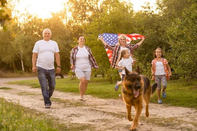 Grande famille marche des drapeaux américains. vue de face, patriotes américains sur la prairie du parc.