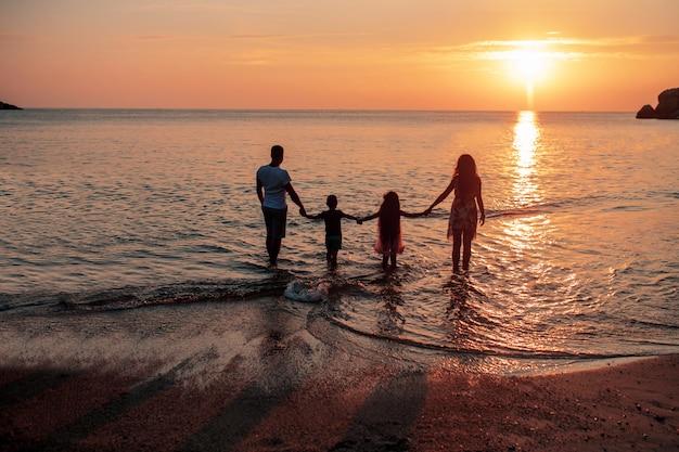 Une grande famille de quatre personnes profite du coucher du soleil. vue arrière