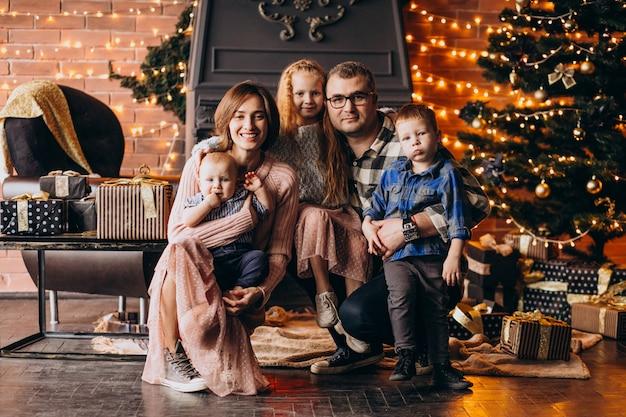 Grande famille la veille de noël avec des cadeaux par l'arbre de noël