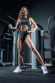 Grande femme athlétique sourit et pose dans la salle de sport avec une barre en métal