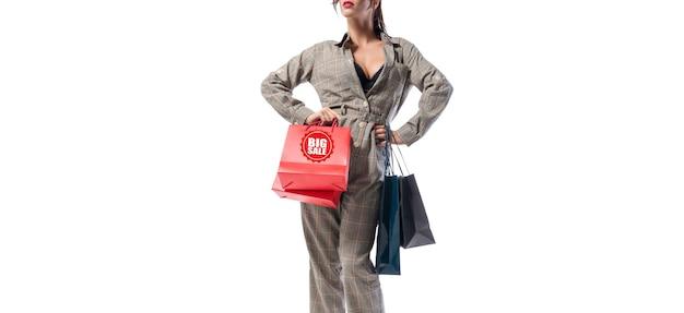 Grande femme élégante posant avec des paquets. sans nom. fond blanc. concept de remises, ventes, achats. technique mixte