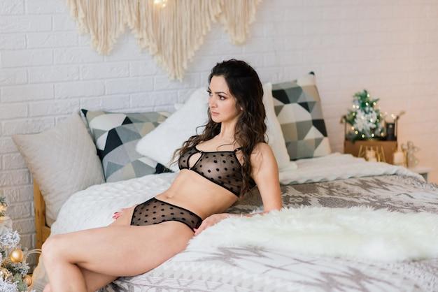 Grande femme mince en lingerie sexy dans l'atmosphère de noël.