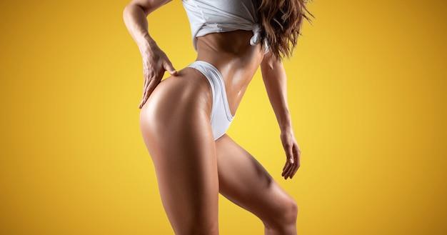 Grande femme qui pose en studio sur fond jaune. longues jambes. concept de soins de la peau. technique mixte