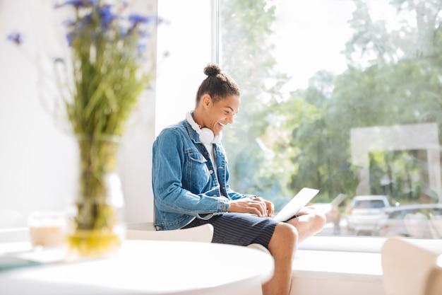 Grande fenêtre. une gentille brune garde le sourire sur son visage tout en travaillant sur son ordinateur portable