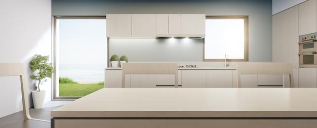 Grande fenêtre en verre près du comptoir et armoire de cuisine moderne avec vue sur la mer dans une maison de plage d'été de luxe.