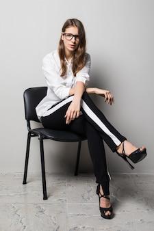 Grande fille brune à lunettes habillée en t-shirt blanc et pantalon noir est assise sur une chaise de bureau en face de fond blanc