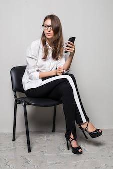Grande fille brune à lunettes habillée en t-shirt blanc et pantalon noir est assise avec téléphone sur chaise de bureau en face de fond blanc