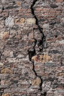Grande fissure dans le vieux mur de pierre. vue verticale