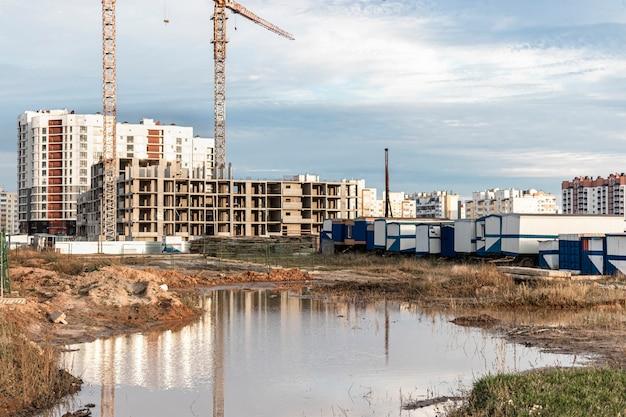 Une grande flaque d'eau après la pluie sur le chantier de construction d'un grand établissement résidentiel. reflet dans l'eau du chantier de construction et des grues sur fond de ciel coucher de soleil.