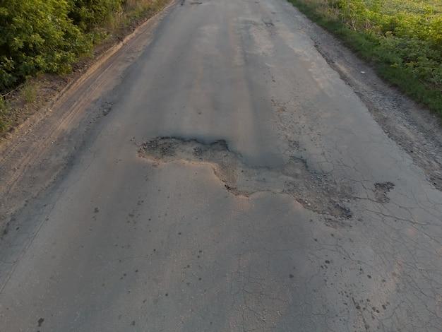 Une grande fosse s'est formée sur la route goudronnée. nid de poule sur l'ancienne surface de la route.
