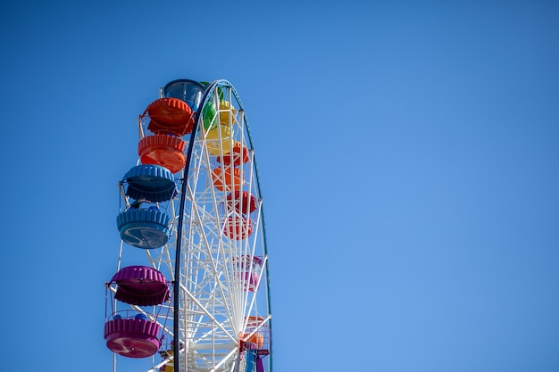Une grande grande roue contre un ciel bleu. des stands avec des gens montent. il y a une place pour le texte. concept : animations les vacances d'été, vacances avec enfants le week-end, balades en manèges.