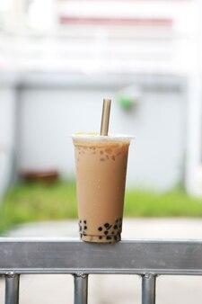 Grande et grande tasse de thé au lait glacé avec bulle boba boisson fraîche et sucrée style taiwan mis sur la barre d'acier et fond flou, concept de nourriture et de boisson