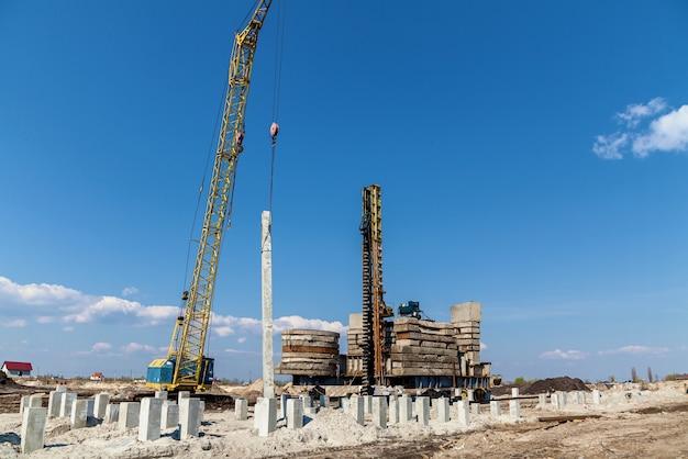 Une grande grue travaillant avec une façade d'un immeuble résidentiel sur fond de ciel bleu pur.