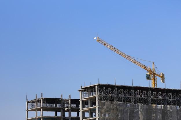 Grande grue de l'usine de machinerie lourde ou d'un immeuble en copropriété sur fond de ciel bleu.