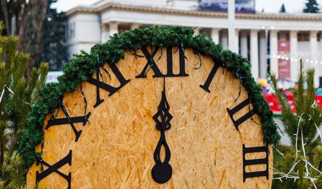 Grande horloge en bois vintage dans le parc d'hiver rappelle que la nouvelle année arrive