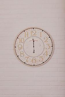 Grande horloge murale ronde sur le mur montre près de douze heures.